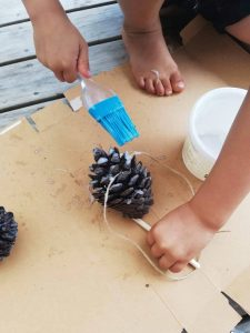 Painting the melted coconut oil on to the pine cone